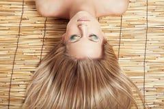 Frauenkopf mit Verfassung auf Bambusmatte Lizenzfreie Stockfotos