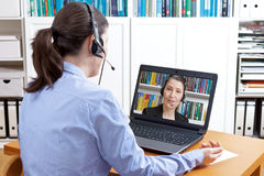 Frauenkopfhörer-Computer-Videoanruf Stockfoto