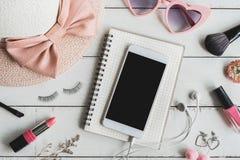 Frauenkosmetik und Modeeinzelteile mit intelligentem Telefon lizenzfreie stockbilder