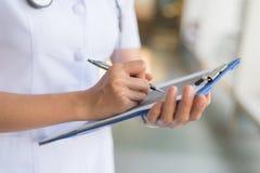 Frauenkrankenschwester im weißen Mantel berichtet in einem Notizbuch lizenzfreie stockfotos