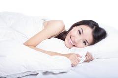 Frauenlächeln-Gesichtsabschluß, der oben auf dem Bett liegt Lizenzfreie Stockbilder
