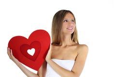 Frauenlächeln mit roter Herzform in der Hand Stockfotografie