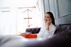 Frauenlächeln und -gespräch am Telefon stockbild