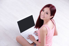 Frauenlächeln unter Verwendung des Laptops Lizenzfreie Stockfotos
