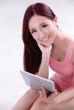 Frauenlächeln unter Verwendung des Tabletten-PC Stockfotografie