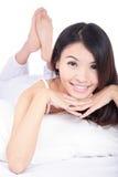 Frauenlächelngesicht beim Lügen auf dem Bett Stockbilder