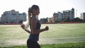 Frauenläufe durch das Stadion bei Sonnenuntergang Langsame Bewegung stock footage