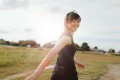 Frauenläufer, der auf Feld am Morgen geht Stockbild