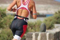 Frauenläufer, der auf Triathlonrennen läuft Lizenzfreie Stockfotos
