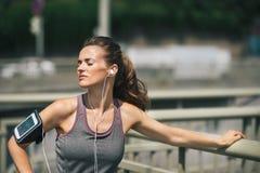 Frauenläufer, der eine Pause im Sonnenschein hört Musik macht lizenzfreie stockfotos