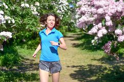 Frauenläufer, der im Frühjahr Park mit lila Blüte, Morgenlauffreien, Eignung und dem Laufen rüttelt lizenzfreies stockfoto