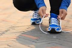 Frauenläufer, der Spitzee auf Stadtstraße bindet Stockbild