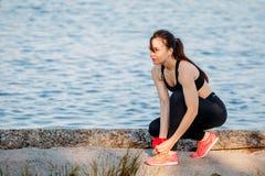 Frauenläufer, der Spitzee auf Turnschuhen auf Strand bindet lizenzfreies stockbild