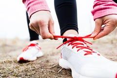 Frauenläufer, der Sportschuhe bindet Lizenzfreie Stockbilder
