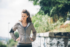 Frauenläufer mit den Händen auf den Hüften, die weg Abstand untersuchen stockbild
