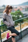 Frauenläufer mit den Händen in den Taschen, die an der Leitschiene sich lehnen lizenzfreie stockfotografie