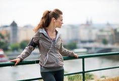 Frauenläufer mit Kopfhörern im Profil, herauf gegen Leitschiene lizenzfreie stockfotos