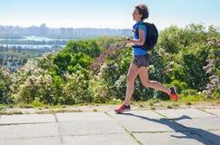 Frauenläuferlauf tauscht aus, um mit Rucksack, Stadtmorgenlaufdem austauschen und Eignungskonzept zu arbeiten lizenzfreie stockfotografie