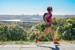 Frauenläuferlauf tauscht aus, um mit Rucksack, Stadtmorgenlaufdem austauschen und Eignungskonzept zu arbeiten stockfotografie