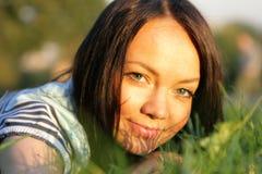 Frauenlüge auf dem Gras lizenzfreies stockfoto