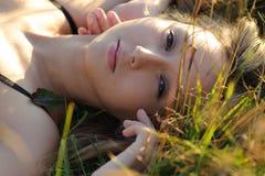 Frauenlüge auf dem Gras Stockbild