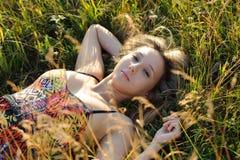 Frauenlüge auf dem Gras Lizenzfreie Stockfotografie