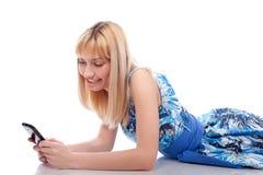 Frauenlüge mit Handy auf einem Weiß Lizenzfreie Stockfotos