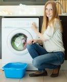 Frauenladen kleidet in die Waschmaschine im Haus stockfotos