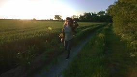 Frauenlandwirt läuft entlang die Straße entlang dem Feld Glaubt einer Richtung der Freiheit von der Stadt und vom Geschäft Herein stock video footage