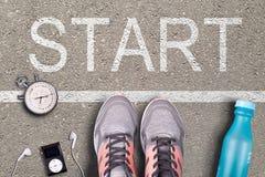Frauenlaufschuhe und -ausrüstung auf Asphalt Whit beginnen Aufschrift Laufendes Training auf harten Oberflächen läufer stockfotografie