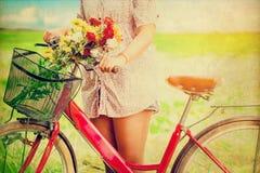 Frauenlebensstil im Frühjahr mit bunten Blumen im Korb des roten Fahrrades Lizenzfreie Stockfotografie