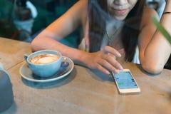 Frauenlebensstil unter Verwendung eines Handys im Cafékaffee lizenzfreies stockbild