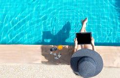 Frauenlebensstilspiellaptopentspannendes nahes Luxusswimmingpool sunbath, Sommertag am Strandurlaubsort im Hotel