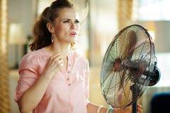 Frauenleiden von der Sommerhitze bei der Stellung vor Fan stockfoto