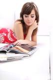 Frauenleseart und weisezeitschrift auf Sofa Stockbild