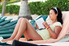 Frauenlesebuch auf dem Strand Stockbilder