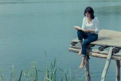 Frauenlesebuch auf der Bretttabelle nahe See Lizenzfreie Stockfotografie