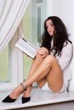 Frauenlesebuch auf Fensterrahmen Lizenzfreies Stockbild