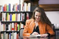 Frauenlesebuch in der Bibliothek Lizenzfreies Stockfoto
