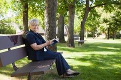 Frauenlesebuch in einem Park Lizenzfreies Stockbild