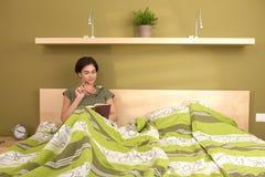 Frauenlesebuch im Bett lizenzfreie stockbilder