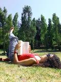 Frauenlesebuch im Park stockbild