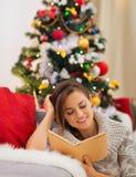 Frauenlesebuch nahe Weihnachtsbaum Lizenzfreie Stockfotografie