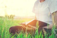 Frauenlesebuch am Parksonnenunterganglicht Lizenzfreie Stockfotografie