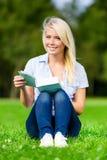 Frauenlesebuch sitzt auf dem grünen Gras Stockbilder