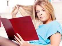Frauenlesebuch und Spielen mit dem Haar Lizenzfreie Stockfotos