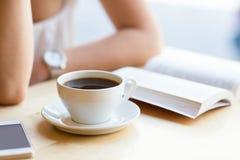Frauenlesebuch und trinkender Kaffee am Café Lizenzfreies Stockfoto