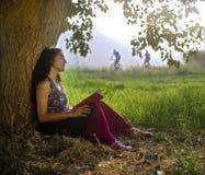 Frauenlesebuch unter Baum Stockfoto