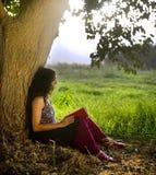 Frauenlesebuch unter Baum Stockfotos
