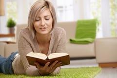 Frauenlesebuch zu Hause Lizenzfreie Stockbilder